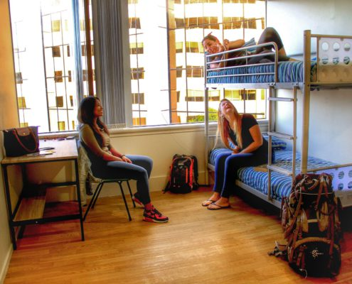 Image of a 4 bed dorm showing 3 people sitting and lying on bunk beds