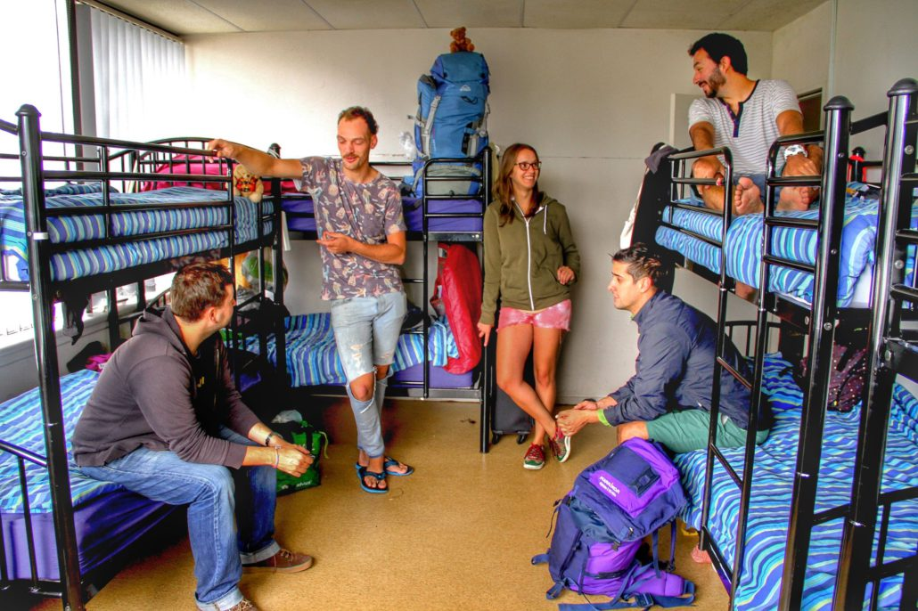 Image of an 8 bed dorm in a backpackers showing some guests standing next to bunk beds