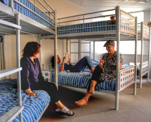 Image of a 6 bed dorm in a backpackers showing guests lying and sitting on bunk beds