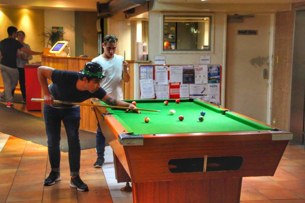 Image of 2 people playing pool in the lobby of the backpacker