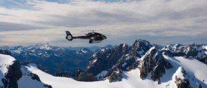 Helicopter flying over snow covered mountains