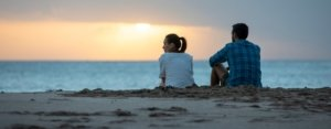couple sitting at the beach watching the sunset